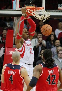 Houston Rockets center Dwight Howard, top, scores as Washington Wizards center Martin Gortat (4) and forward Nene (42) watch during the first half of an NBA basketball game in Houston, Wednesday, Feb. 12, 2014. (AP Photo/Richard Carson)