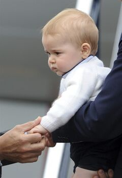 FILE - This is a Wednesday, April 16, 2014 file photo of Britain's Prince George's as his hand is held by New Zealand Governor General Jerry Mateparae as he leaves with his parents Prince William and Kate, the Duchess of Cambridge on a plane bound for Sydney, Australia from Wellington, New Zealand. Prince George turns 1 on Tuesday. While he may be too young to appreciate it, the milestone is causing a nationwide frenzy. Editorial writers call him a symbol of hope, newspaper headlines hail him as