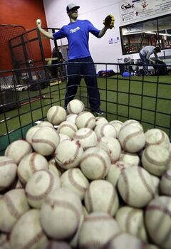 In this Feb. 24, 2014 photo, Kansas City Royals minor league pitcher John Walter, of Haddonfield, N.J., warms up at Power Train Sports Institute's AFC Baseball & Softball Academy in Cherry Hill, N.J. (AP Photo/Mel Evans)