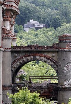 A house is seen beyond the Bannerman's Island Arsenal on Pollepel Island, N.Y., on Tuesday, June 5, 2012. Though it looks like it was built to withstand battering rams, it was actually a surplus military goods warehouse made to resemble a Scottish castle. Businessman Francis Bannerman VI had it built early in the 20th century as a place to store helmets, haversacks, mess kits and munitions he could not store in his thriving shop in Manhattan. (AP Photo/Mike Groll)