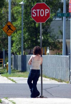 A young prostitute waits at a stop sign for her next customer.