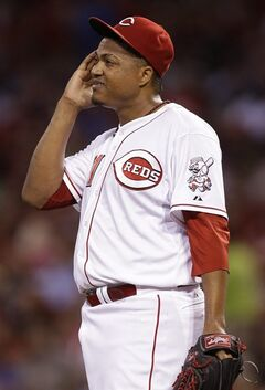 Cincinnati Reds starting pitcher Alfredo Simon wipes his face in the seventh inning of a baseball game against the Chicago Cubs, Wednesday, July 9, 2014, in Cincinnati. Simon pitched six and two-thirds innings, giving up one run, in winning his 12th game of the season 4-1. (AP Photo/Al Behrman)