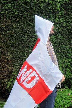 A man models a wearable England flag, made by Asda, in London, Friday, May 30, 2014. British supermarket chain Asda has been criticized for launching a wearable England flag ahead of the World Cup that some customers say resembles an outfit worn by U.S. far-right organization the Ku Klux Klan. Designers of the flag _ a St. George's Cross with the word 'England' on it _ included a white hood so fans could stay dry while wearing it. (AP Photo/PA, Carmel Wilkinson) UNITED KINGDOM OUT NO SALES NO ARCHIVE