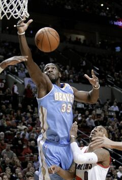 Denver Nuggets forward Kenneth Faried, left, pulls in a rebound over Portland Trail Blazers guard Damian Lillard during the first half of an NBA basketball game in Portland, Ore., Thursday, Jan. 23, 2014. (AP Photo/Don Ryan)