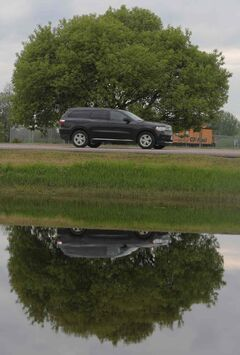 Water in the ditches along First Street North create a mirror-like reflection of a passing SUV heading north in this file photo.