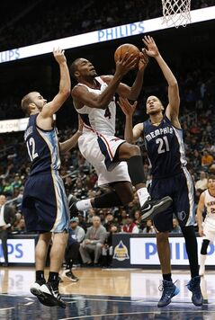 Atlanta Hawks forward Paul Millsap (4) is fouled as he drives between Memphis Grizzlies' Nick Calathes (12) and Tayshaun Prince (21) during the first half of an NBA basketball game Saturday, Feb. 8, 2014, in Atlanta. (AP Photo/John Bazemore)