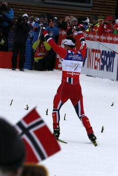 Marit Bjoergen of Norway celebrates as she crosses the finish line to win the Ladies 7.5 km Classic + 7.5 km Free Skiathlon of the Nordic Ski World Championships in Val di Fiemme, Italy, Saturday, Feb. 23, 2013. (AP Photo/Giovanni Auletta)