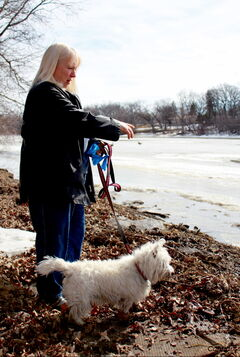 Woodhaven resident Brenda Macdonald surveys the water level on the Assiniboine River behind her home. She doesn't anticipate major flooding to affect her home.