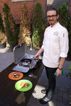 Chef Marcus Monteiro poses with a couple of his dishes in this recent handout photo. Escaping the city for a few days of camping doesn't have to mean getting away from delicious food, says a chef who takes pleasure in elevating his menu from those old standbys, burgers and hot dogs. Marcus Monteiro, who grew up camping with his family near Bobcaygeon in the Kawartha Lakes area of Ontario, still enjoys roughing it under canvas. But when it comes to his food, the executive chef at Brassaii Restaurant and Lounge in Toronto prefers to create easy, healthful and tasty alternatives to the packaged and processed fare that many tote along for their outdoor experience. THE CANADIAN PRESS/HO - Canadian Tire