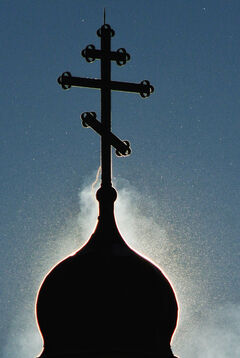 Steam and blowing snow swirl around one of the crosses on the Holy Trinity Ukrainian Orthodox Metropolitan Cathedral that is silhouetted by the sun early Sunday morning. Dec. 09, 2012