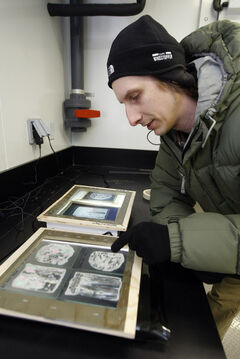 Jens Ehn, assistant professor of environment and geography, studies slices Actic ice in his cold -lab facility.