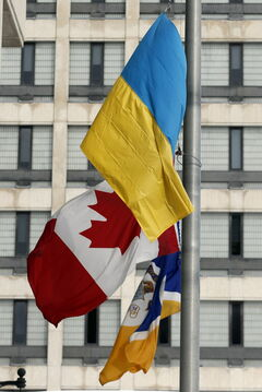 The City of Winnipeg flag, Canadian flag and Ukrainian flag all stand at half mast in front of Winnipeg City Hall.
