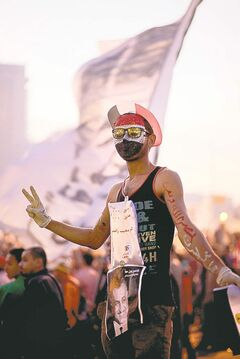 A protester wears a mask in the colours of the Egyptian flag in Tahrir Square.