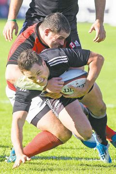 New Zealand Maori All Blacks Tim Bateman (right) is tackled by Canada's Aaron Carpenter.