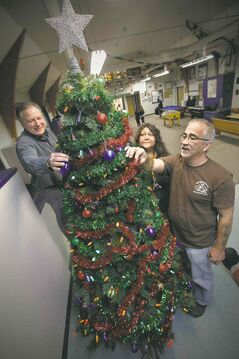 Rossbrook House staffers Phil Chiappetta (from left) Valerie Henderson and Warren Goulet put the  finishing touches on the Christmas tree.
