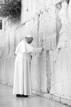 Pope Francis places an envelope in a crack between the stones of the Western Wall in Jerusalem.