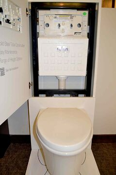 Modern toilets can be more compact because the plumbing required to operate them is mounted in the 2 by 4-inch divider wall behind the fixture.
