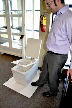Jason Petroff of The Ensuite demonstrates the automatic lid opening feature of this $6,700 toilet and bidet by Kohler.