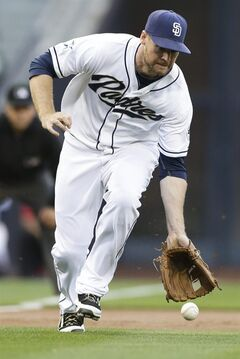 San Diego Padres third baseman Chase Headley can't reach a ground ball in time as Washington Nationals' Ian Desmond arrives safely to first during the first inning of a baseball game Friday, June 6, 2014, in San Diego. (AP Photo/Gregory Bull)