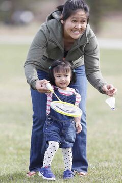 Genelee Delacruz and her daughter, Rylee Chiyo, play badminton with dad, Rudy, at Assiniboine Park Saturday.
