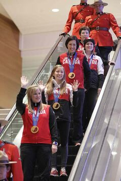 Olympic curling gold medalists Jennifer Jones (skip), Kaitlyn Lawes (third), Jill Officer (second), Dawn McEwen (lead), Kirsten Wall (alternate) and their coach Janet Arnott return to hundreds of family and supporters in Winnipeg Monday.