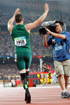 FILE - this is a Tuesday Sept. 16, 2008 file photo of Oscar Pistorius of South Africa, left, as he waves in front of a cameraman after he won the gold medal in the Men's 400m T44 final at the Beijing 2008 Paralympic Games in Beijing, China. With more global broadcast coverage than ever before, the London 2012 Paralympic Games in London will win its largest ever live television audience, except in the United States, where no events will be screened live by a traditional broadcaster, prompting complaints from some equality campaigners.(AP Photo/Andy Wong, File)