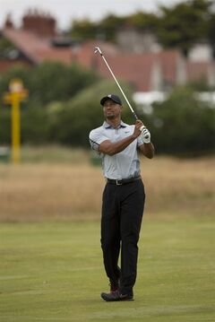 Tiger Woods of the US walks plays a shot on the 1st fairway during a practice round at the Royal Liverpool Golf Club prior to the start of the British Open Golf Championship, in Hoylake, England, Saturday, July 12, 2014. The 2014 Open Championship starts on Thursday, July 17. (AP Photo/Jon Super)