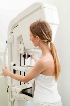 A woman preparing to receive a mammogram.