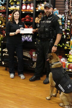 Westwood Pet Valu owner presents a cheque to Const. Jadkiewicz of the Winnipeg K9 Unit.