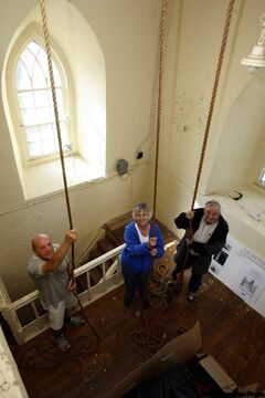 From left: Peter Clarke, Barbara Gessner and Bill Gessner hold bell ropes at St. Andrew's-on-the-Red Anglican Church. The large brass bells were imported from England in 1849.