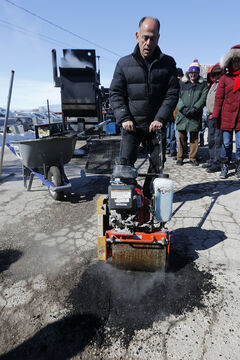 Saverio Marra of Pelletpatch dumped several pails of mix into his Asphalt Patch Master machine, which heated it to about 180 C,  and then shovelled the compound into the pothole and packed it with a roller.