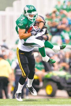 Roughriders slotback Weston Dressler grabs a pass before being brought down by Hamilton Tiger-Cats defensive back Courtney Stephen on Sunday in Regina.