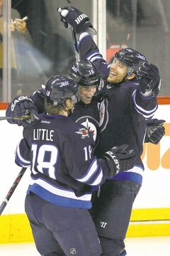 John Woods / The Winnipeg Free Press archives Celebrating a score, Jets Bryan Little, Andrew Ladd and Blake Wheeler (from left) will be brothers in arms again in the coming season.