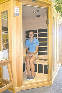 Gwen Brockman of LCL Spas and Billiards enjoys the comfortable interior of a two-person plug-in far infrared sauna by Saunatec, the largest sauna manufacturer in the world.