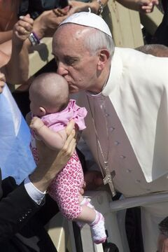 Pope Francis kisses a baby as he arrives in St.Peter's Square at the Vatican for his weekly general audience, Wednesday, June 26, 2013. (AP Photo/Andrew Medichini)
