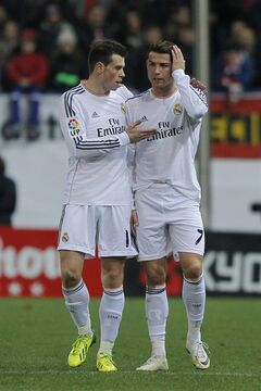 Real's Cristiano Ronaldo talks to Gareth Bale, after Ronaldo fouls Atletico's Javi Manquillo during a semi final, 2nd leg, Copa del Rey soccer match between Atletico de Madrid and Real Madrid at the Vicente Calderon stadium in Madrid, Spain, Tuesday, Feb. 11, 2014. (AP Photo/Andres Kudacki)