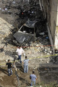 Investigators work at the scene of a Beirut car bomb attack that killed eight people including Brig. Gen. Wissam al-Hassan, head of the intelligence division of Lebanon's domestic security forces, on Friday.  Protesters burned tires and set up roadblocks around Lebanon on Saturday in a sign of boiling anger over the devastating attack that threatened to bring Syria's civil war to Lebanon.