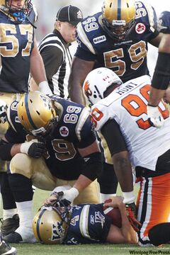 Winnipeg Blue Bombers' Buck Pierce (4) lies on the ground after being hit hard by B.C. Lions' Solomon Elimimian in second half CFL action in Winnipeg, Thursday, July 28, 2011. Pierce was pulled from the game after this set of plays and replaced by Alex Brink (7).