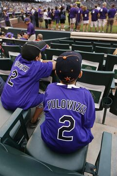Young fans wear misspelled jerseys given to fans with the name of Colorado Rockies All-Star shortstop Troy Tulowitzki before a Rockies against the Pittsburgh Pirates baseball game in Denver, Saturday, July 26, 2014. (AP Photo/David Zalubowski)