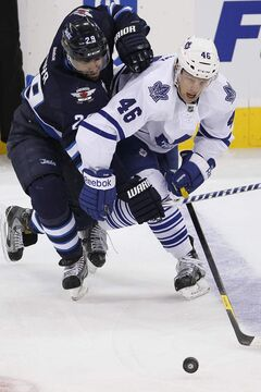 Winnipeg Jets' Johnny Oduya (29) and Toronto Maple Leafs' Joey Crabb (46) jostle for the puck during first-period action.
