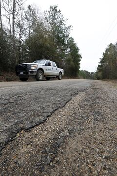 In this Dec. 23, 2013 photograph, a pickup truck passes on River Road in Amite County, Miss. County Supervisor Max Lawson says the drilling-based road damage is of great concern throughout the small county as county government has limited funds for road repair. Lawson hopes the oil companies plan a big increase in drilling activity in 2014 in southwest Mississippi does not drain the road repair fund that must cover the entire county. (AP Photo/Rogelio V. Solis)