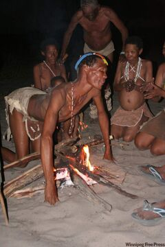 A village medicine man kneels over the fire during the end of the healing trance dance in the Kalahari Desert in northwestern Botswana.