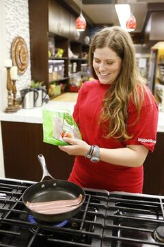 This image released by NBC shows contestant Rachel Frederickson preparing food during an episode of