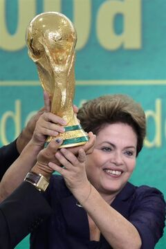 FILE - In this June 2, 2014 file photo, Brazil's President Dilma Rousseff holds up the 2014 World Cup trophy after it was officially presented to Rousseff by FIFA President Sepp Blatter, during a ceremony at the Planalto presidential palace, in Brasilia, Brazil. Rousseff met Friday, July 11, 2014 with a group of foreign journalists in Brasilia, where she hailed Brazil proved skeptics wrong who said the nation couldn't organize a successful World Cup, and said it boded well for its hosting of the 2016 Summer Olympics in Rio de Janeiro. (AP Photo/Eraldo Peres, File)