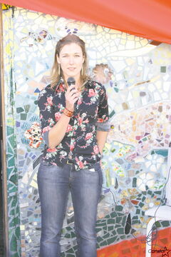 Artist Annie Bergen speaks at the unveiling of a mosaic mural on the side of the Red Road Lodge located on the corner of Logan Avenue and Main Street.