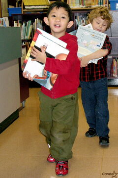 King Edward Community School students Gavyn (foreground) and Dustin haul away their chosen books during a special book drive at the school on Dec. 20.
