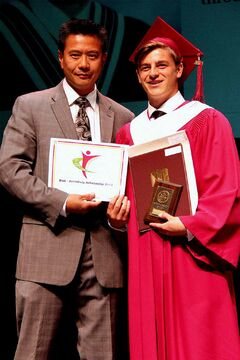 Ray Louie of the Headingley Regional Chamber of Commerce presents a Leaders of Tomorrow Scholarship to Matthew McCorquodale-Bauer at the Westwood Collegiate graduation ceremony.