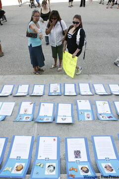 Women look at the placards of slain and missing women in front of the Manitoba legislature in Winnipeg in August. People gathered at the legislature to call for a task force to look into the cases.