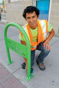 Fernando Trejo bolts down a bike rack into the cement on Ellice Avenue.
