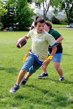 Grade 6 Pinkham School student Gage Walker dekes a defender on the rush attack at the Inner City Youth Football Program season finale at Frank Whyte Field on June 25.
